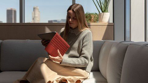 A woman sits on a couch opening Surface Pro 7  with a Poppy Red Type Cover