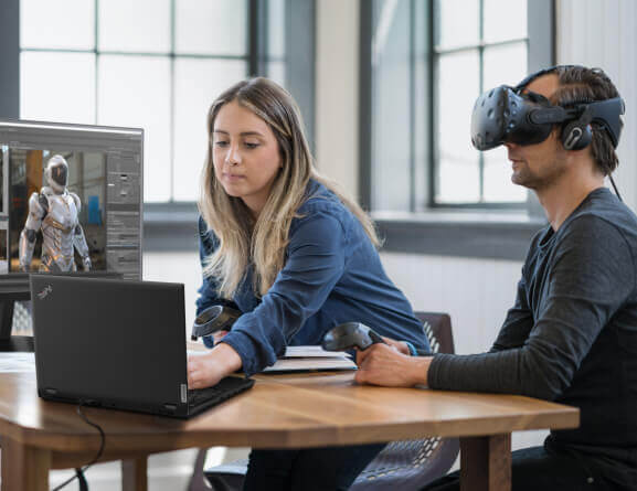 Rear view of Lenovo ThinkPad P15 laptop sitting on a table in front of two individuals using virtual reality equipment