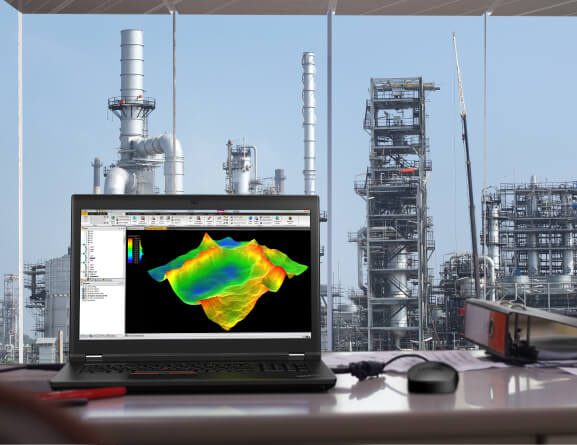 Headshot of Lenovo ThinkPad P17 mobile workstation on a desk overlooking an oil and gas site.