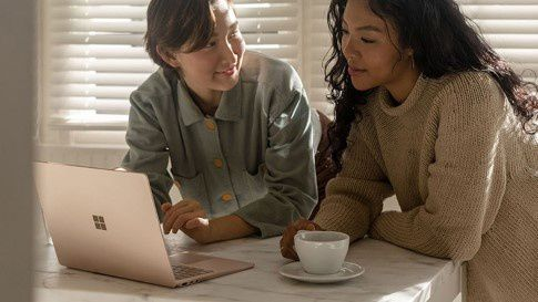 Two women sit at a dining table in front of a Surface Laptop 3