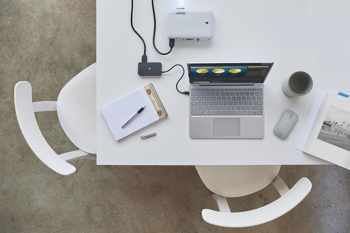 Surface Laptop Go pe un birou, conectat la un proiector