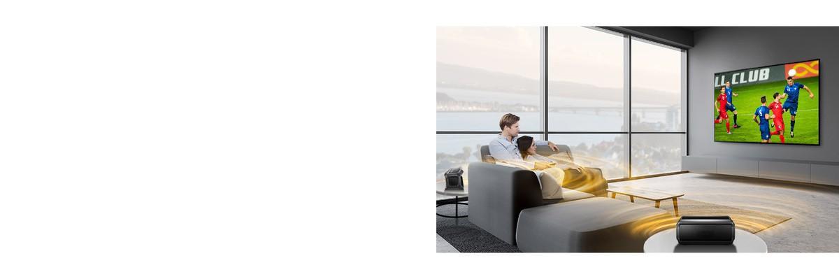 Muškarac i žena gledaju sportsku utakmicu na televizoru u dnevnoj sobi sa stražnjim Bluetooth zvučnicima