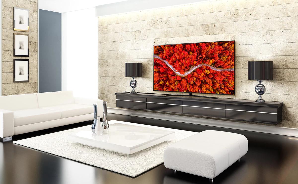 O cameră de zi de lux cu un televizor care afisează o vedere aeriană a pădurii de culoare rosie.