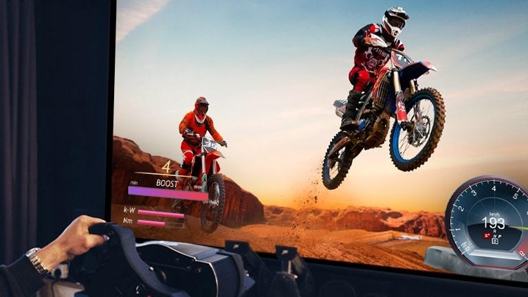 Prim-plan cu un jucător ce joacă un joc de curse de biciclete pe un ecran TV.