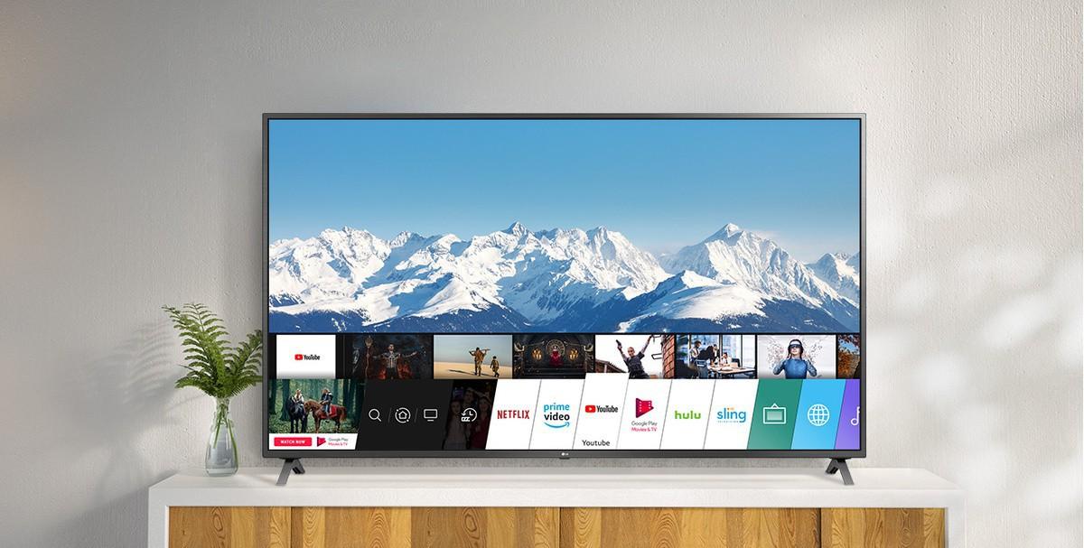 Televizor amplasat pe un suport alb, pe un perete alb. Ecranul TV prezintă ecranul principal cu webOS.