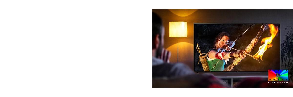 Un bărbat stă pe canapea si urmăreste un film de actiune. Fata de la televizor tine în mână un arc întins la maximum si o săgeată.