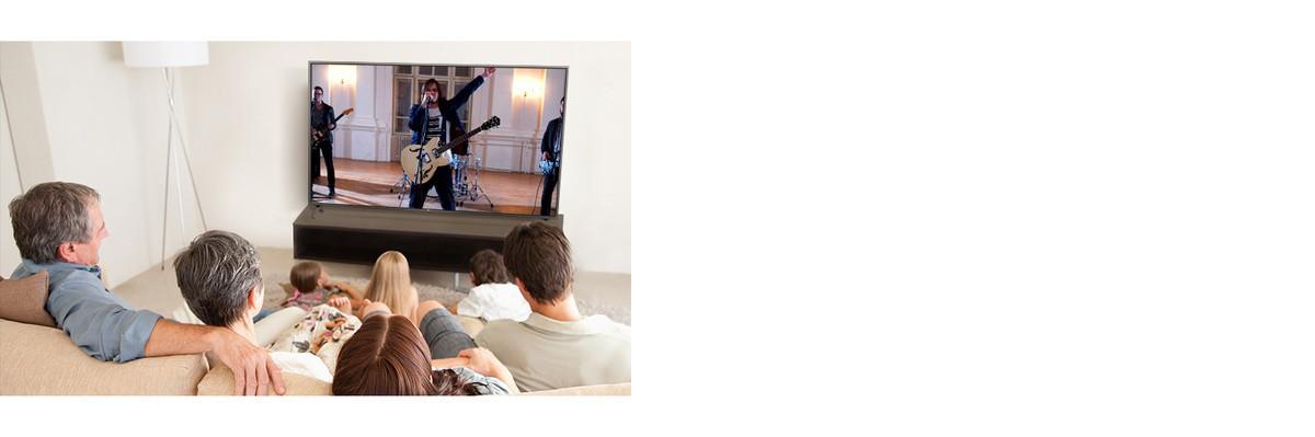 O familie cu sapte membri stau în camera de zi si se uită la un film. Pe ecranul TV apare o formatie care cântă.