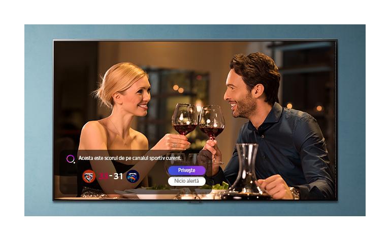 Imaginea unui bărbat si a unei femei ciocnind pahare, afisată pe un ecran TV în timp ce se primesc notificări ale alertelor sportive