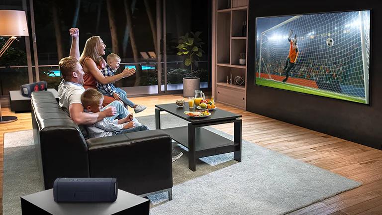 O familie asezată pe o canapea uitându-se la fotbal la TV