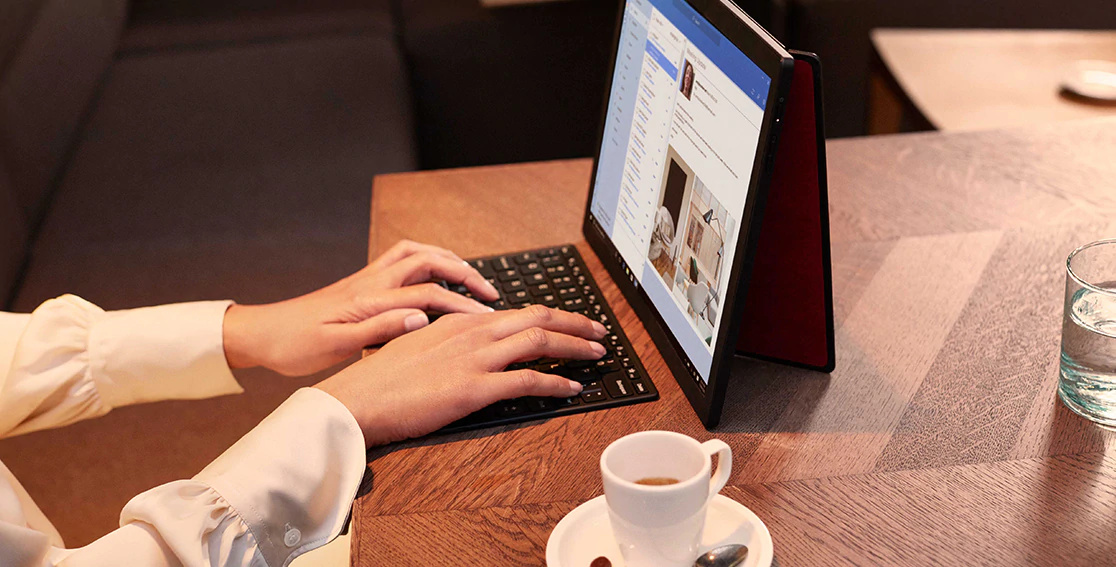 Woman\'s hands typing on a wireless keyboard, answering email on Lenovo ThinkPad X1 Fold open full screen with back cover stand.